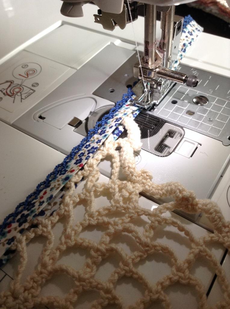 Deckchen mit der Schnittkante in das Schrägband legen und fest nähen